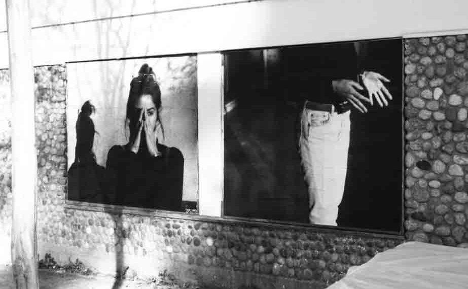 Popnographe colle des affiches aux messages féministes sur les murs de Toulouse